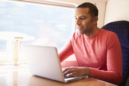 Man Using Laptop On Train Stock Photo