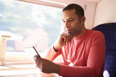 african american male: Man Reading E Book On Train Stock Photo