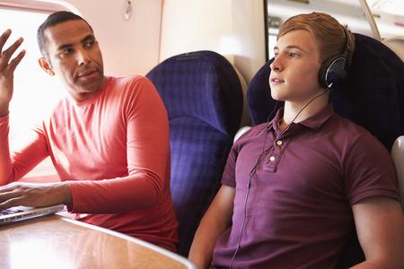 시끄러운 음악과 함께 기차 승객을 방해하는 젊은 남자 스톡 콘텐츠