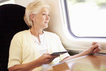 e reading: Senior Woman Reading E Book On Train Journey