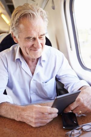 Senior Man Reading E Book On Train Journey Standard-Bild