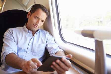 and the horizontal man: Man Reading E Book On Train Stock Photo