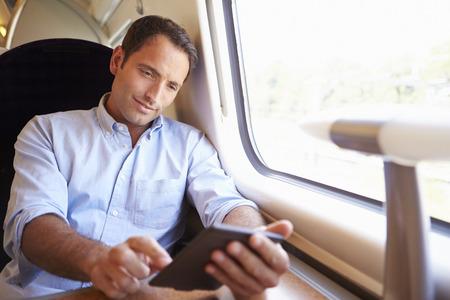 Man Reading E Book On Train Фото со стока