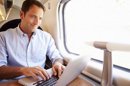 Hombre que usa la computadora portátil en el tren