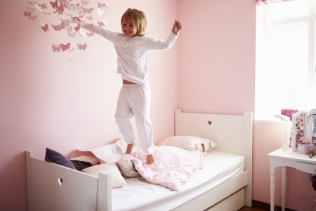 Young Girl Jumping On Her Bed photo