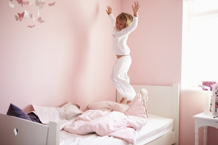 air jump: Young Girl Jumping On Her Bed