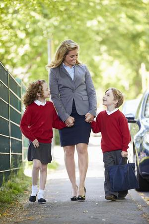 Moeder lopen naar school met kinderen op weg naar het werk