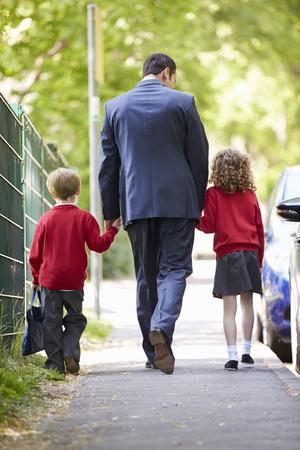 Père de marche à l'école avec les enfants sur le chemin de travail