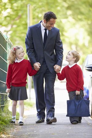 padres hablando con hijos: Padre que recorre a la escuela con los ni�os en camino a su trabajo