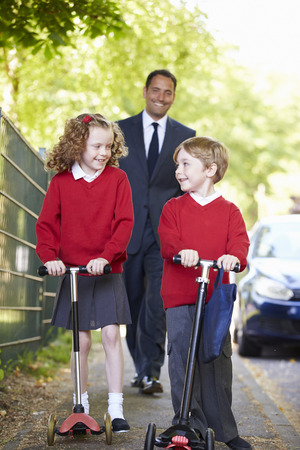 Children Riding Scooters On Their Way To School With Father photo