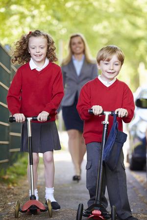 escuela primaria: Ni�os que montan Scooters en su camino a la escuela con la madre