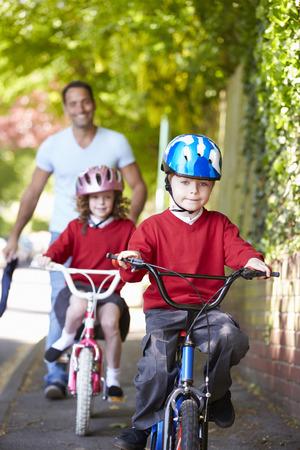 niños caminando: Los niños que montan las bicis en su camino a la escuela con el padre