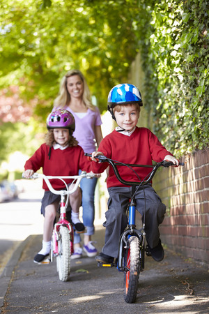 padres hablando con hijos: Los ni�os que montan las bicis en su camino a la escuela con la madre Foto de archivo