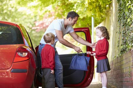 padres hablando con hijos: Padre Conducir a la escuela con ni�os Foto de archivo