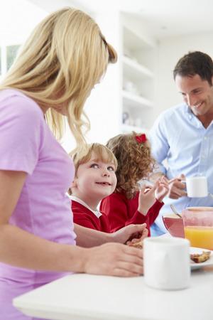 Family Having Breakfast In Kitchen Before School photo