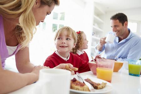 uniform school: Familia que tiene el desayuno en cocina Antes de la escuela