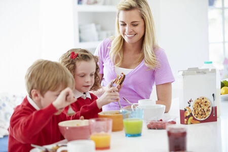 Mother And Children Having Breakfast In Kitchen Together photo
