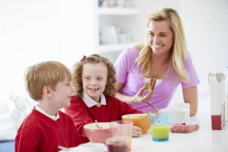 niños desayunando: Madre y niños que desayunan en la cocina junto
