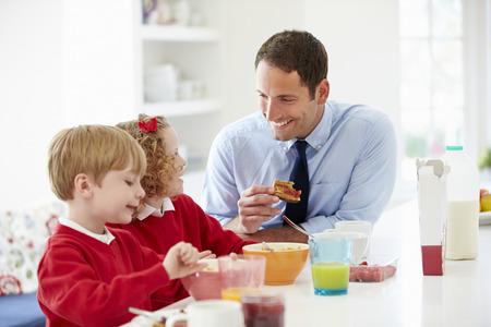 Vader En Kinderen Die Ontbijt In Keuken Samen Stockfoto