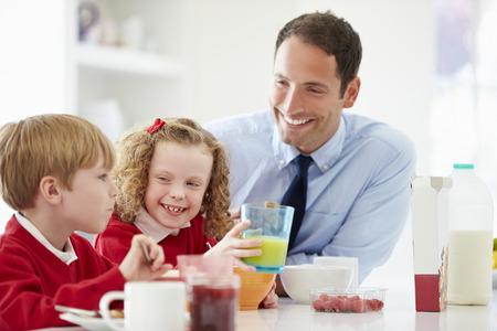 niños desayunando: Padre y niños que desayunan en la cocina junto