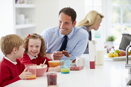 Family Having Breakfast In Kitchen Before School And Work photo