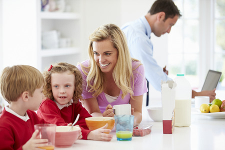 breakfast cereal: Family Having Breakfast In Kitchen Before School And Work
