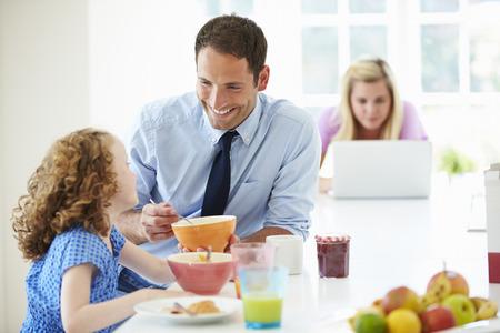niños desayunando: Padres e hija que desayunan en la cocina junto Foto de archivo