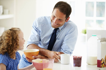 niÑos hablando: Padre e hija que desayunan en la cocina junto Foto de archivo