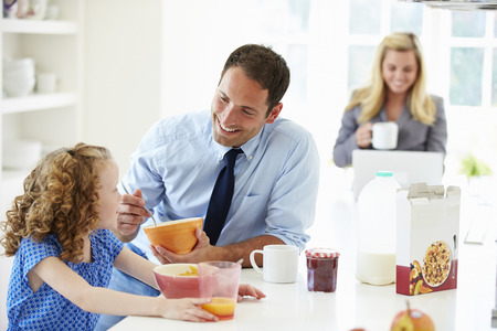 Parents And Daughter Having Breakfast In Kitchen Together photo