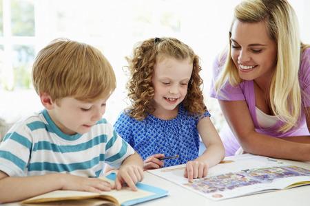 niños leyendo: Madre ayudar a los niños con la tarea en la cocina
