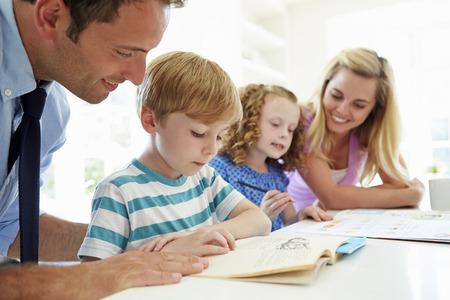 madre trabajando: Padres Ayudando a niños con la tarea en la cocina