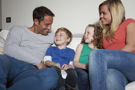 niÑos hablando: Familia que se sienta en el sofá que ve la TV junto Foto de archivo