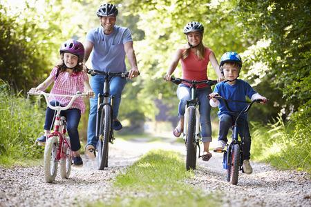 家庭: 家人騎自行車在農村 版權商用圖片