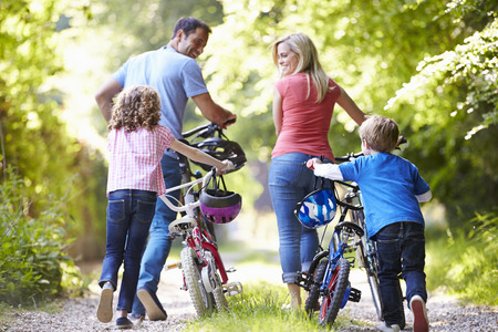 Family Pushing Bikes Along Country Track photo
