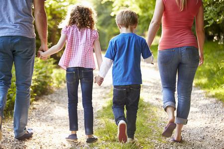 cogidos de la mano: Vista posterior de la familia que recorre en campo
