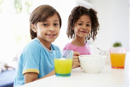 Two Children Having Breakfast In Kitchen Together photo