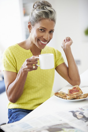 Mature Woman Eating Breakfast And Reading Newspaper photo