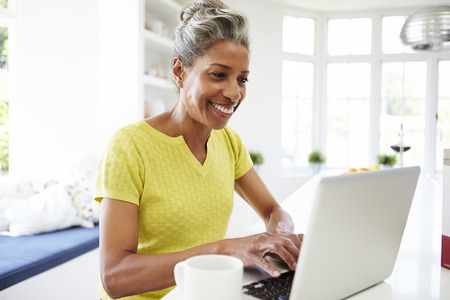 African American Woman Using Laptop In Kitchen At Home photo