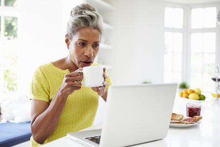women black: Mujer del afroamericano usando la computadora port�til en la cocina en el hogar