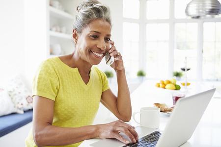 working at home: Mujer que usa la computadora port�til y hablando por tel�fono en la cocina de su casa