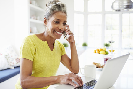 Woman Using Laptop And Talking On Phone In Kitchen At Home photo