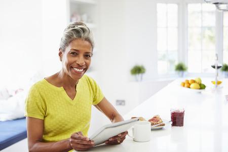 mujeres maduras: Mujer del afroamericano que usa la tablilla digital en el hogar