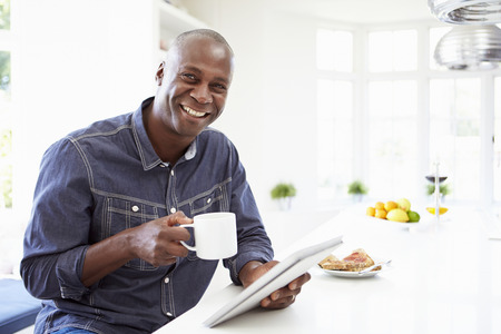 man coffee: African American Man Using Digital Tablet At Home