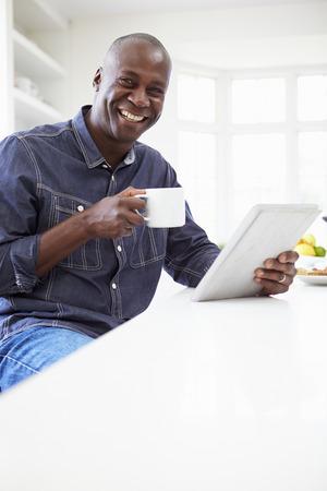 descansando: Hombre del afroamericano que usa la tablilla digital en el hogar