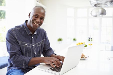 hombres negros: African American Man uso portátil en casa Foto de archivo