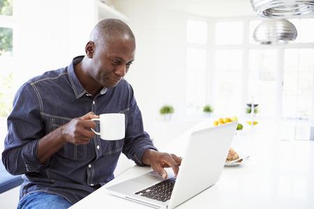 drinking coffe: African American Man uso port�til en casa Foto de archivo