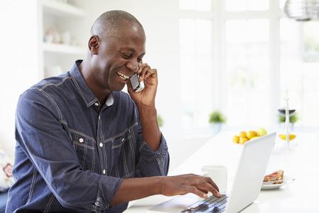 남자 랩톱 및 집에 부엌에서 전화로 얘기