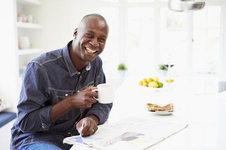 아프리카 계 미국인 사람을 먹는 아침 식사와 신문을 읽는
