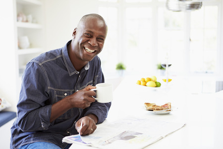 African American Man Eating Breakfast And Reading Newspaper photo