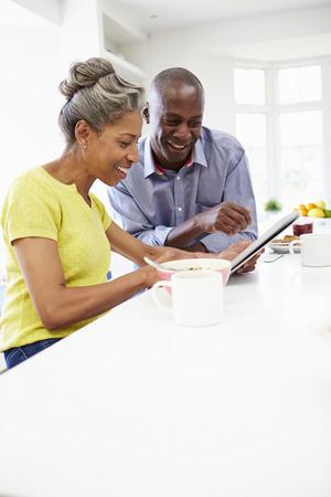 couple afro americain: Couple afro-am�ricain d'�ge m�r utilisant tablette num�rique � la maison